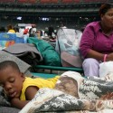 Two-year-old Erroll Thomas sleeps peacefully as his mother Selika Thomas sits in the background Saturday, Sept. 4, 2005 at Houston's Astrodome.  Evacuees from New Orleans, Thomas and her family hope to start over in Atlanta. (AP Photo/Pat Sullivan)