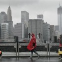 Peter Cusack, center, and Mel Bermudez walk their dogs Teague, left, and Molly along the Brooklyn waterfront beneath the New York skyline as Hurricane Sandy advances on the city, Monday, Oct. 29, 2012. Hurricane Sandy continued on its path Monday, forcing the shutdown of mass transit, schools and financial markets, sending coastal residents fleeing, and threatening a dangerous mix of high winds and soaking rain.  (AP Photo/Mark Lennihan)