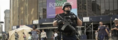 Members of New York's National Guard stand next to a tent structure, back left, while a member of the NYPD Counterterrorism Division, monitors outside Penn Station during a joint anti-terrorism drill on Friday, July 27, 2012 in New York.  (AP Photo/Bebeto Matthews)