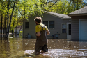 Man walking in flooded waters by a house